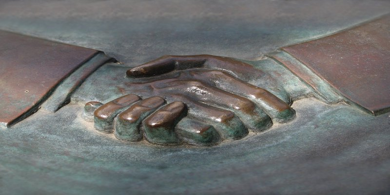 handshake carved in metal