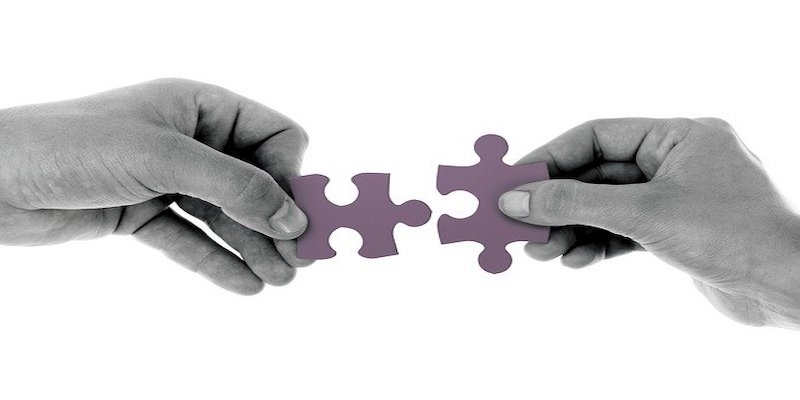 two people holding jigsaw pieces that fit together