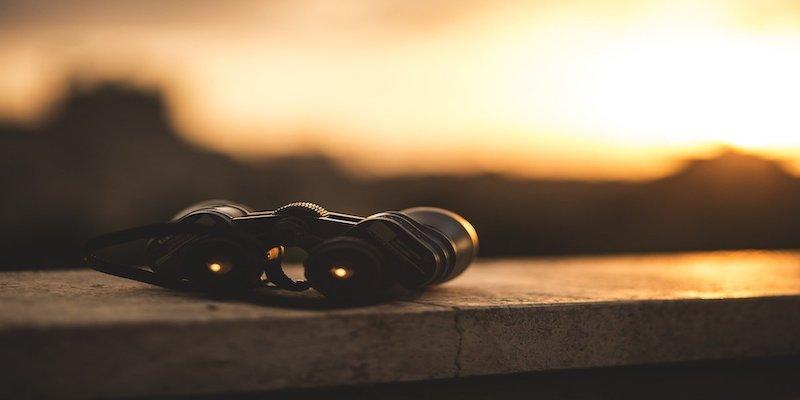binoculars against sunset backdrop