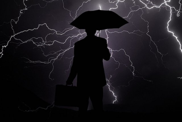businessman under umbrella during storm feature