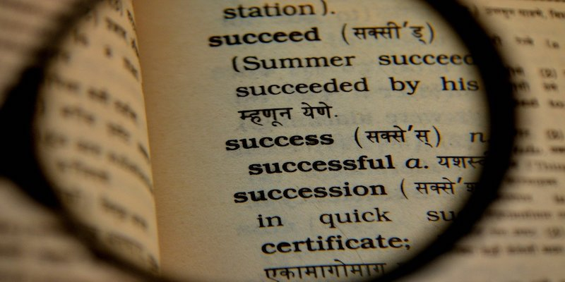 magnifying glass over the word success in dictionary