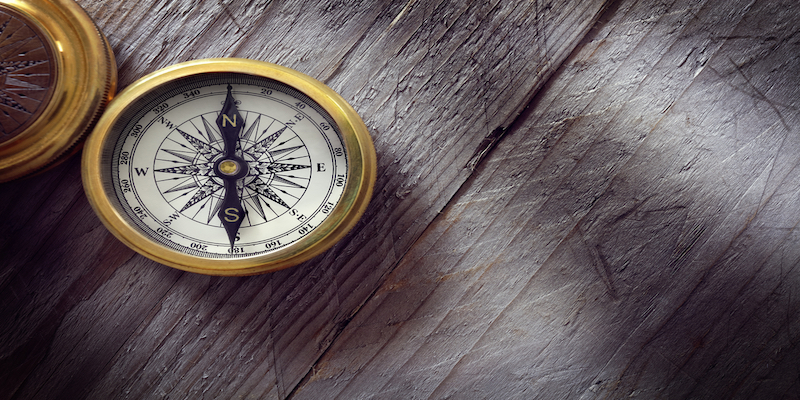 Antique golden compass on wood background